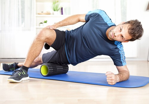 A male exercising with a foam tube on a yoga mat