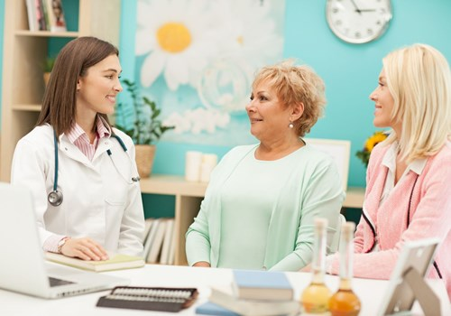 A female doctor talking to an older woman and a younger woman in a floral decorated office
